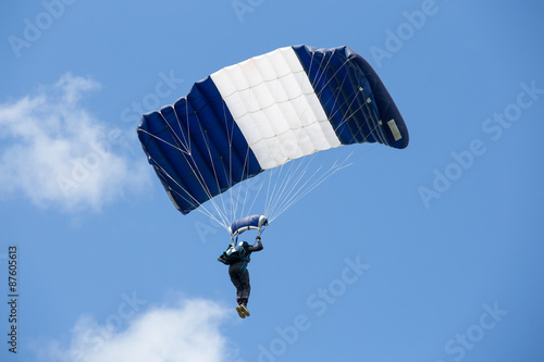 Deurstickers Ballon Parachutist on a striped blue white parachute on bakcground blue sky with clouds