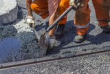 Workers using a shovel to spread mastic asphalt poster