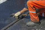Worker using a special tool to spread mastic asphalt 2 poster