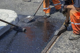 Workers using a asphalt tool to spread mastic asphalt 2 poster