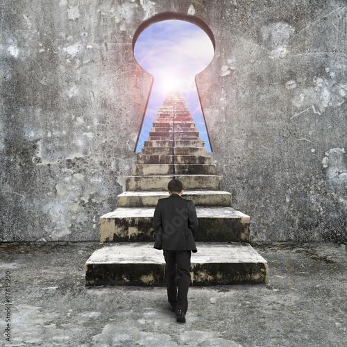 Fototapeta Man climbing old concrete stairs toward keyhole