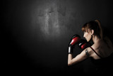 Woman Boxer with Red Gloves on Black Background, high contrast with desaturated grunge filter in studio - 87661696