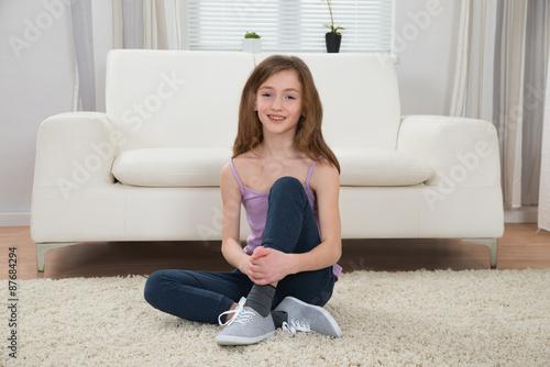 Girl Sitting On Carpet In Living Room