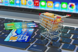 E-commerce, online purchases and internet shopping concept, shopping cart with cardboard boxes and credit cards on laptop keyboard