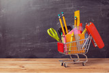 Fototapety Shopping cart with school supplies over chalkboard background. Back to school sale concept