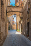 Italian streets with arches on a sunny day and long shadows
