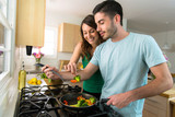 Fototapety Young attractive couple preparing dinner on a date saving money by cooking at home