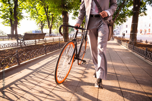Poster businessman walking with bicycle