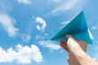 Paper plane against cloudy sky