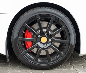 White sports car wheel on the road.