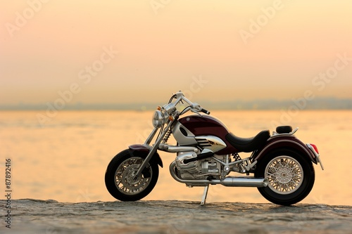 Motorcycle on the rocks in sunset and golden hours плакат