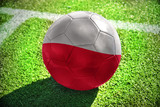 Fototapety football ball with the national flag of poland lies on the green field near the white line