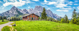 Fototapety Idyllic landscape in the Alps with mountain chalet and green meadows