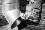 Teenager in sneakers kicks drainpipe, black and white poster
