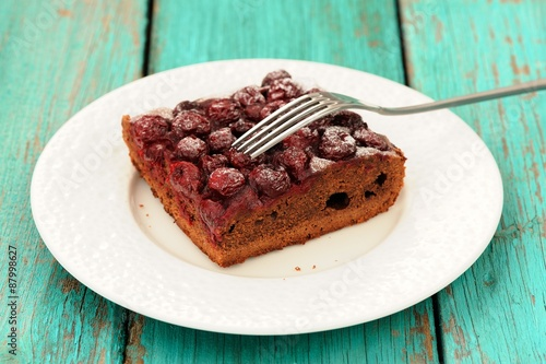 Delicious homemade cherry chocolate pie with fork in white plate © alexeyborodin