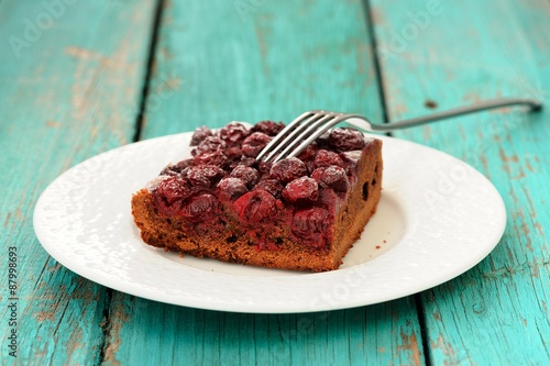 Piece of delicious homemade cherry chocolate pie with fork in wh © alexeyborodin