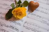 Gelbe Rose und Herz auf einem Notenblatt