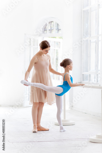 The little ballerina posing at ballet barre with personal Plakát