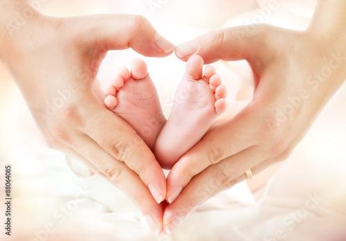 fototapeta na ścianę Stopy dziecka w rękach matki - kształt palenisko