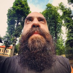 super bearded bald man serious taking selfie from the bottom