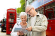 senior couple with map on london in city street