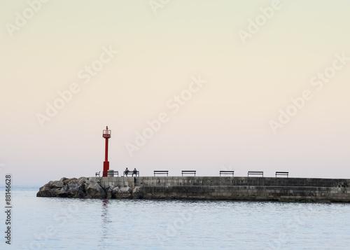 Leinwanddruck Bild Warten auf den Sonnenaufgang an der Mole