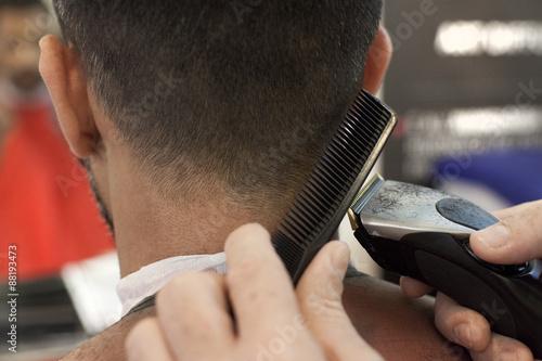 Poster, Tablou Un parrucchiere mentre taglia i capelli
