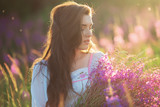 Fototapety happy young girl smiling, holding hands in lavender. Soft focus,