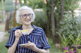 Grandma having cup of coffee outdoors