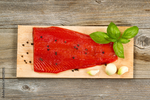 Poster Fresh red salmon fillet on cedar cooking plank with spices and h