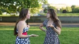 Young cute lasses talking among themselves outdoors. Teenage girls gossiping. poster