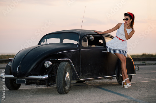 obraz lub plakat Beautiful pin-up girl posing with hot road car