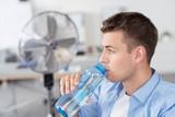 Fototapety mann trinkt wasser im büro mit ventilator im hintergrund