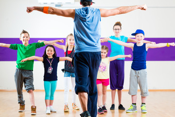Dance teacher giving kids Zumba fitness class