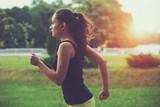 Fototapety Pretty sporty woman jogging at park in sunrise light
