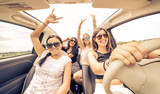 Fototapety four girls driving in a convertible car and having fun