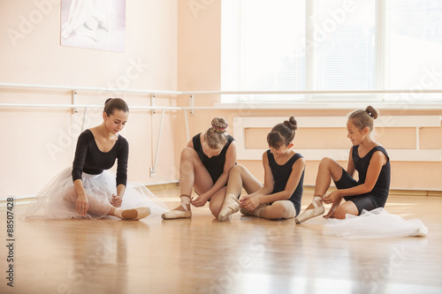 Young ballerinas putting on pointe shoes while sitting on floor in ballet class Plakát