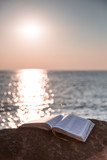 Fototapety The bible on a stone against the sea