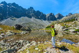 Young woman tourist knelled on edge of small lake in Starolesna valley, High Tatra Mountains, Slovakia poster