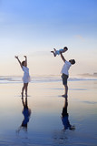 Fototapety Positive family - father, mother with baby son relax with fun on smooth black sand sea beach. Healthy lifestyle, active parents, and people outdoor activity on tropical summer holidays with children