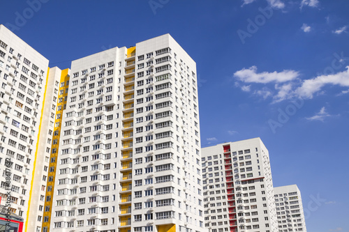 Multistory new modern apartment building against the blue sky