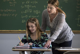 Fototapety Female teacher helping a young female student