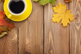 Fototapety Autumn leaves and coffee cup over wood background