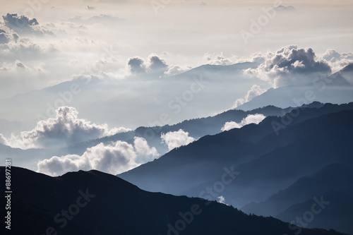 Beautiful misty sunrise. Brightly lit fog and cloud mountain valley landscape.  - 88697281