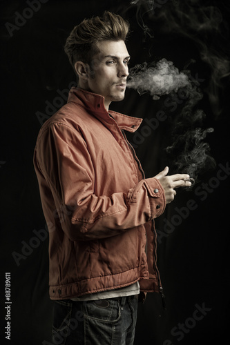 Poster Handsome young man smoking cigarette, dressed as James Dean