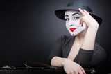 Portrait of woman mime with a suitcase