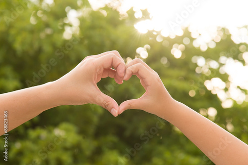Mother and her child holding hands in heart shape framing on nat