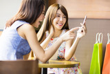 Fototapety happy young woman looking at phone in coffee shop