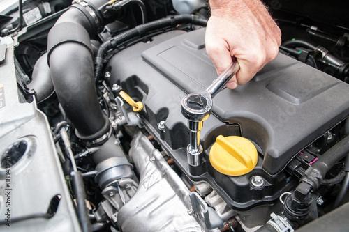 Mani che riparano un motore di automobile con una chiave
