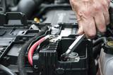 Mani che serrano il morsetto della batteria nel motore di un'automobile con una chiave - 88848446